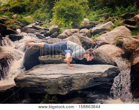 Young sporty fit woman doing yoga asana Eka Pada Koundinyasana 1 at tropical waterfall. Vintage retro effect filtered hipster style image.