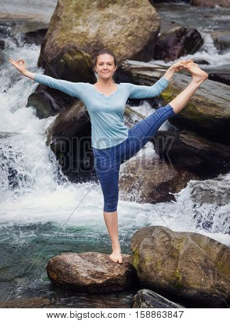 Yoga outdoors - woman doing Ashtanga Vinyasa Yoga balance asana Utthita Hasta Padangushthasana - Extended Hand-To-Big-Toe Pose position posture at waterfall. Vintage retro hipster style image.