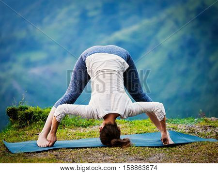 Yoga exercise outdoors -  woman doing Ashtanga Vinyasa Yoga asana Prasarita padottanasana  D - wide legged forward bend pose outdoors. Vintage retro effect filtered hipster style image.