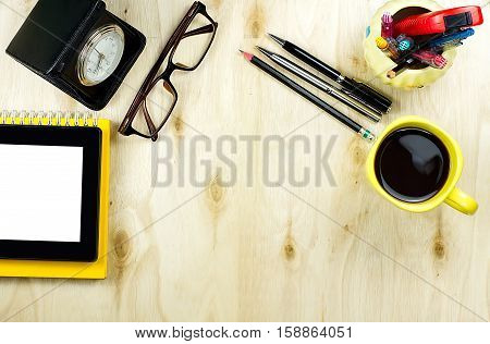 Tablet PC with blank screen on yellow notebook with cup of coffee glasses clock and office supply on wooden background with copy space floor. Office table desk in top view.