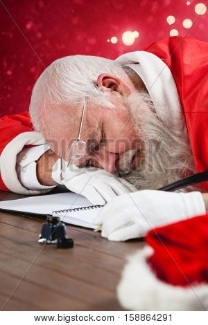 Tired Santa Claus napping at desk while writing a letter with a quill against light design shimmering on red
