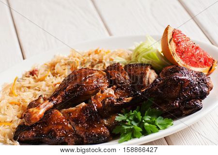 Grilled duck served with stewed cabbage and grapefruit slice. Tasty meal of brown roasted poultry with vegetable, white wooden background. Dining, appetizing, Christmas food concept