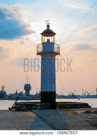 Lighthouse silhouette. Seaport of Varna at sunset. Bulgaria