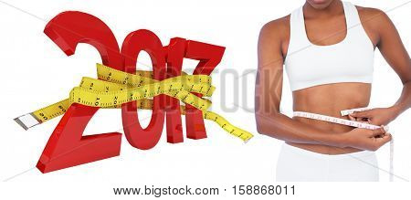 Young woman measuring her waist against digitally generated image of 3D new year with tape measure