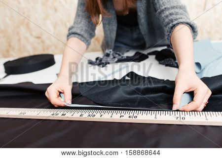 Hands of designer at work with fabric close-up. Tailor measuring necessary amount of material for sewing cloth. Garment industry, tailoring process, pattern cutting concept