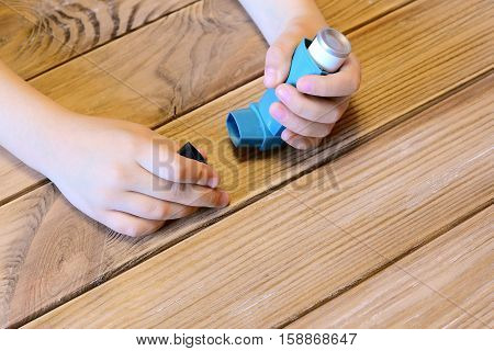 Small kid opens asthma inhaler. Inhalation treatment of respiratory diseases. Allergy and bronchial asthma medication. Old wooden background
