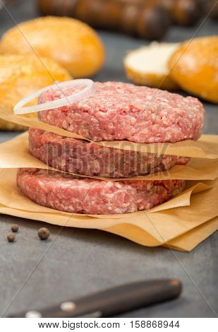 Close up raw ground beef meat cutlets with onion ring on a stone surface