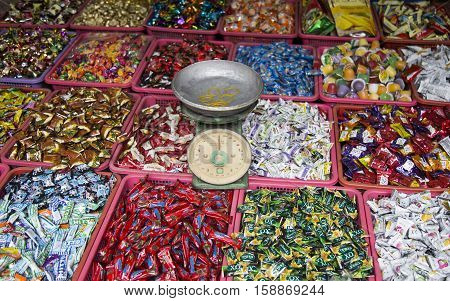 Hanoi, Vietnam - Nov 26, 2016: Many kind of candies of many local Vietnamese brands with a balance for whole sale and retail on the side walk of Hang Buom old quarter street.