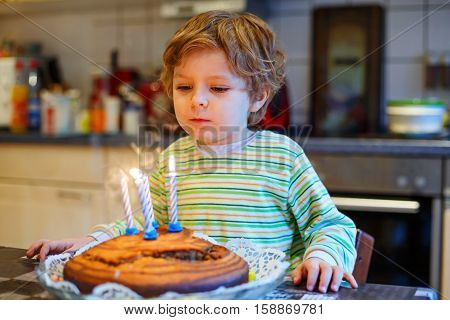Happy little kid boy celebrating his birthday and blowing candles on homemade baked cake, indoor. Birthday party for children. Carefree childhood, anniversary, happiness. 4 years old