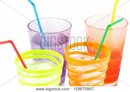Plastic glasses with water ice cubes and straws on white background.