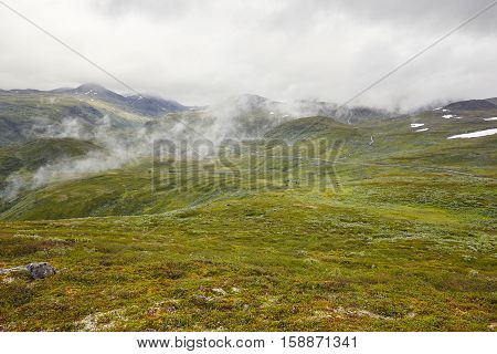 Norwegian green mountain landscape with secondary road. Norway highlight. Horizontal