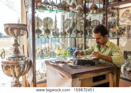 Iran, Isfahan - December 13, 2015: An old skilled artisan makes traditional metal souvenirs in a small workshop.