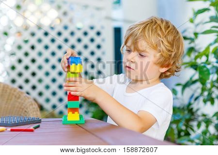 Cute little kid boy with glasses playing with lots of colorful plastic blocks indoor. Active child having fun with building and creating of tower. Promotion of skills and creativity