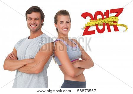 Portrait of a sporty young couple with arms crossed against digitally generated image of 3D new year with tape measure