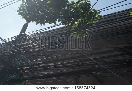 Tangled and messy electrical cables in Bangkok city, Thailand