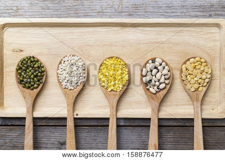 Group of beans with spoon on wood table background