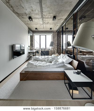 Bedroom in a loft style with brick wall and concrete ceiling. There is a TV, bed with pillows, lamps with lampshades, wardrobe with glass sliding doors, tables, armchair, carpet on the floor.
