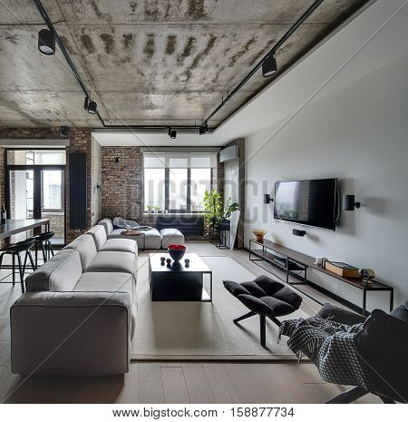 Sitting-room in a loft style with white and brick walls and a concrete ceiling. There are light sofas, wooden tables, different chairs, armchair, TV, lamps. On the floor there is a parquet and carpet.