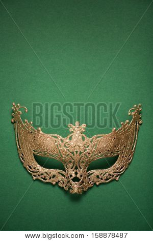 Female carnival golden mask on green background. Top view