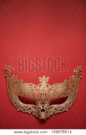 Female carnival golden mask on red background. Top view