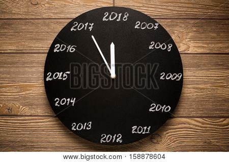 Concept of clock on the eve of 2018. Wooden background.