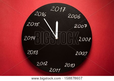 Concept of clock on the eve of 2017. Red background.