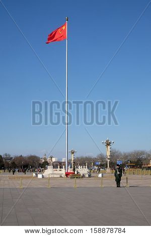 BEIJING, CHINA - FEBRUARY 23, 2016: Soldiers guard the Chinese flag in Tiananmen Square. It's the third largest square in the world and important site in Chinese history, in Beijing, China.