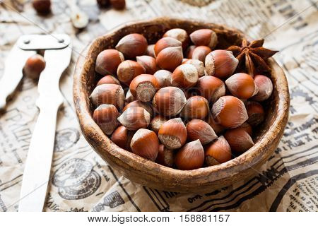 Hazelnuts in a bowl on old vintage newspaper, horizontal, close up view