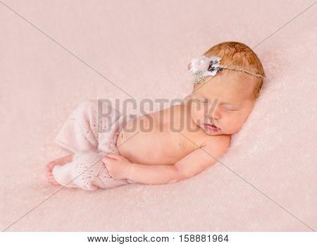 cute sleeping newborn in panties and headband on his head on pink blanket