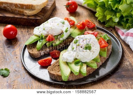 Close up view of delicious poached egg and avocado toasts garnished with chopped parsley. Selective focus