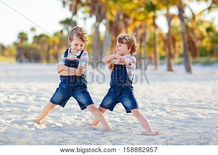 Two little kids boys having fun on tropical beach, happy best friends playing, friendship concept. Siblings brothers, twins in family look with palms on background. Family vacations on ocean
