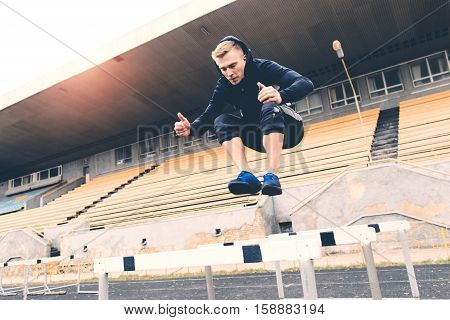 Young athlete jumping over a hurdle during a workout on a treadmill at the old stadium
