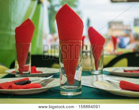 Picture of the dining-table served with red napkin close up. White plates with flatware and red napkin against the blurred background of the guests of a restaurant.