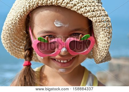 Happy child with glasses on the nose with sunscreen on the face