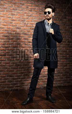 Full length portrait of a well-dressed imposing man in sunglasses. Fashion hair styling, barbershop. Brick wall background.
