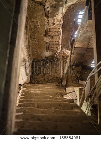 Picture of the old wooden down stairs in the belfry. Wooden stairs opposite the molder wall of the church. The sunlight shining feebly through the slit between red planks of the wooden frame.