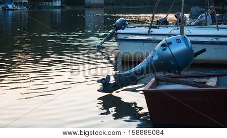 Picture of the fishing boat with outboard motor in the shallow river. Fishing boat with beige - coloured bottom anchoring on the river shore. Motor boat fastened on the mirror.