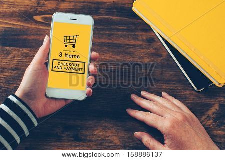 Woman holding modern mobile phone with online shopping app ready to checkout and make electronic payment on internet