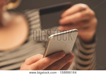 Woman using smartphone app to check e-wallet account balance close up of hands with mobile phone and plastic credit card