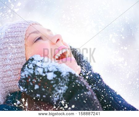 Winter young woman portrait. Beauty Joyful Model Girl touching her face skin and laughing, having fun in winter park. Beautiful young woman laughing outdoors. Enjoying nature, wintertime