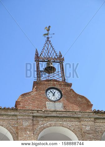 Church belfry with weather vane and clock on sunny day Andalusia Spain