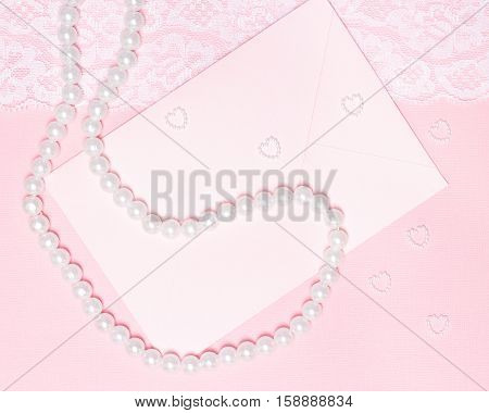 Close-up of envelope, pearl chaplet and small hearts made of beads on pink textured background with white lace. Love letter, wedding invitation