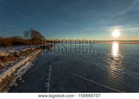 ice with cracks at the coast of the lake on a winter decline