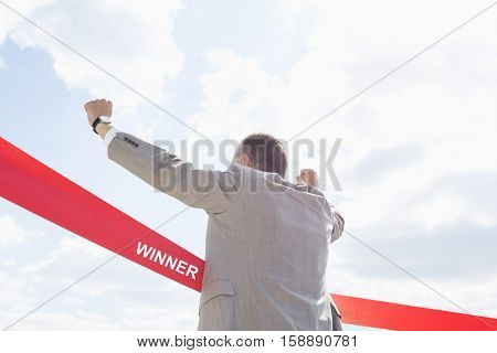 Rear view of businessman crossing finish line against sky with text saying winner