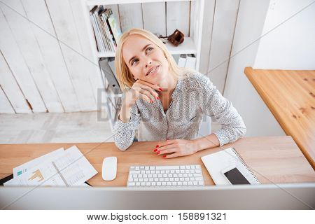 Portrait of a pensive wondered young business woman sitting at her workplace and thinking about something