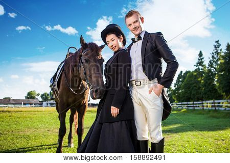 Portrait of confident well-dressed couple standing with horse on field