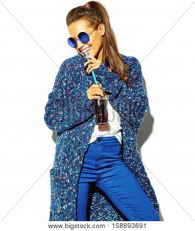 portrait of beautiful happy cute brunette woman model in casual blue hipster summer clothes with no makeup isolated on white in sunglasses drinking cola from bottle with straw
