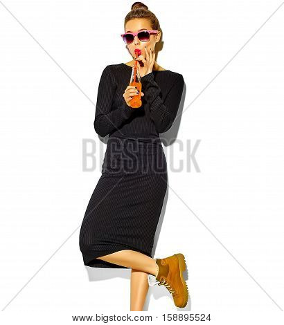 portrait of beautiful crazy smiling brunette woman model in casual hipster summer black dress clothes with red lips isolated on white drinking soda from bottle with straw in sunglasses