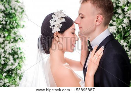 Side view of romantic multi-ethnic wedding couple