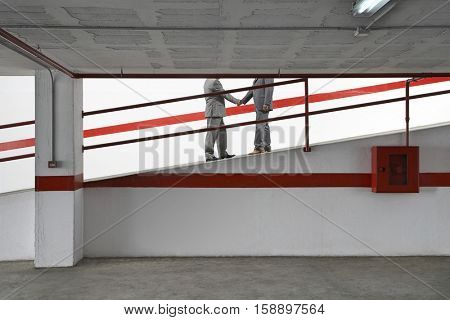 Side view lowsection of two businessmen shaking hands on ramp in parking garage